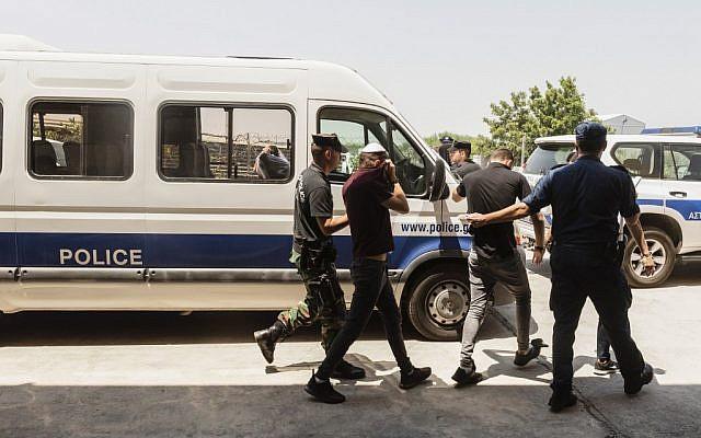 Des touristes israéliens, soupçonnés d'avoir violé une jeune Britannique de 19 ans à Ayia Napa, quittent les locaux du tribunal dans la station balnéaire chypriote orientale de Paralimni, le 26 juillet 2019. (Iakovos Hatzistavrou / AFP)
