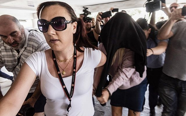 L'adolescente britannique (cachée) qui a accusé sept Israéliens de viol en réunion arrive à la cour de district de Famagusta District Court à Paralimni, à l'est de Chypre, le 29 juillet 2019 (Crédit : Iakovos Hatzistavrou/AFP)