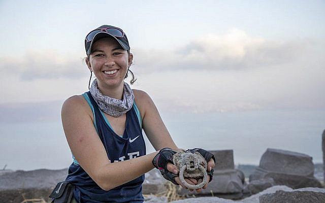 """Jessica Rentz, responsable du site, montre un heurtoir à tête de lion découvert à """"l'église brûlée"""" dans le cadre du projet de fouilles Hippos-Sussita au parc national Susita à l'été 2019. (Autorisation)"""