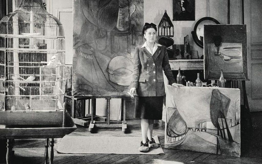 """Dora Maar, rue de Savoie (Paris VIe), par Brassaï en 1943. L'artiste pose devant son tableau """"Nature morte au bocal et à la tasse"""". Huile sur toile. 45,5 x 50 cm. Collection particulière. © Adagp, Paris, 2019. Photo © Centre Pompidou, MNAM-CCI / P. Migeat / Dist. RMN-GP"""
