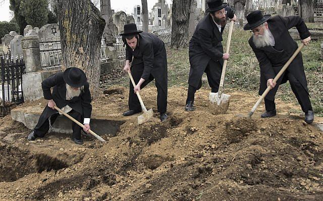 Les rabbins retrouvent les restes des victimes de la Shoah découverts dans une fosse commune au nord du cimetière juif de Iasi, en Roumanie, le lundi 4 avril 2011. Des membres de la communauté juive roumaine ont enterré les restes d'environ 60 Juifs tués par les troupes dans une fosse commune à Popricani, dans le nord de la Roumanie. (Crédit : AP / Radu Aneculaesi / Proimage)