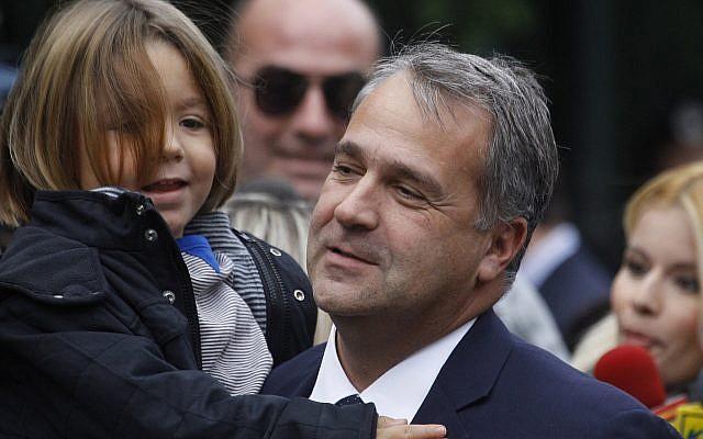 Le nouveau ministre des Transports et des infrastructures Makis Voridis, membre du parti de droite LAOS, au palais présidentiel d'Athènes, son fils dans les bras, le 11 novembre 2011. (Crédit :  Dimitri Messini/AP)