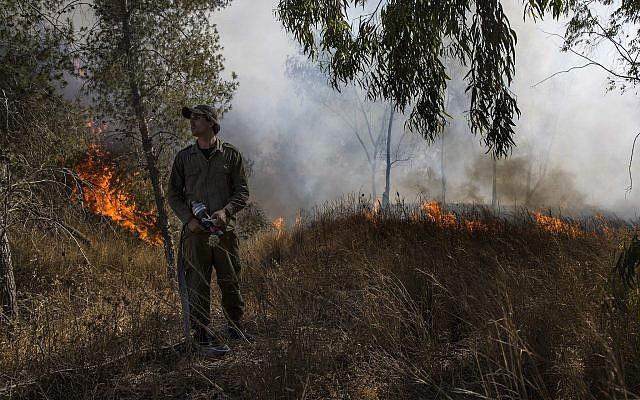 Un soldat israélien combat un incendie déclenché par un engin incendiaire lancé depuis la bande de Gaza dans le sud d'Israël, le 26 juin 2019. (AP Photo/Tsafrir Abayov)