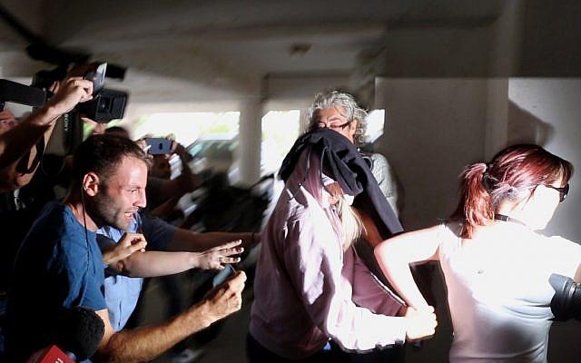 Un agent de police escorte une jeune femme britannique de 19 ans, au centre, vers le tribunal de Famagouste, à Paralimni, à Chypre, le 29 juillet 2019 (Crédit : AP Photo/Petros Karadjias)