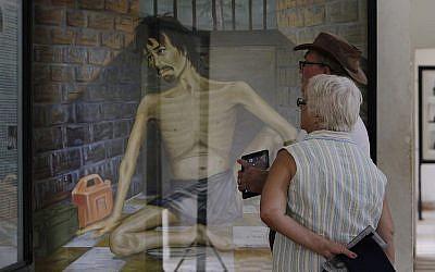 Photo d'illustration : Sur cette photo du 10 juillet 2014, des touristes regardent une peinture dépeignant les tortures des Khmers rouges au musée du génocide  Tuol Sleng, qui était avant la prison Khmer rouge la plus célèbre à   Phnom Penh, au Cambodge (Crédit : AP Photo/Heng Sinith)