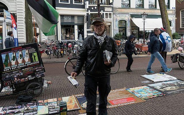 L'activiste BDS Simon Vrouwe fait la promotion du mouvement anti-israélien dans une contre-manifestation à Amsterdam, le 23 avril 2017 (Crédit : Cnaan Liphshiz/JTA)