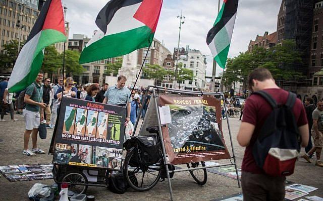 """Des touristes israéliens devant un stand BDS avec des photos et des drapeaux palestiniens, appelant à """"libérer la Palestine"""", sur la place Dam au centre d'Amsterdam, aux Pays-Bas, le 24 juin 2016. (Hadas Parush/Flash90)"""