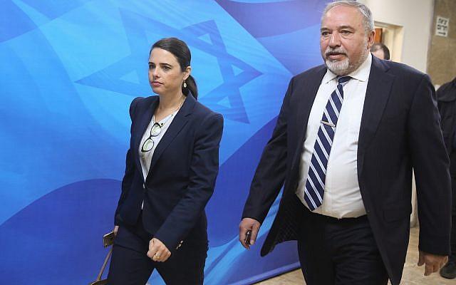 Le ministre de la Défense de l'époque Avigdor Liberman et la ministre de la Justice d'alors Ayelet Shaked arrivent à la réunion hebdomadaire de cabinet au bureau du Premier ministre de Jérusalem, le 17 juin 2018 (Crédit : Marc Israel Sellem/POOL)