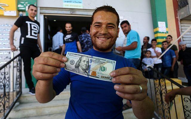Des Palestiniens reçoivent leur aide financière dans le cadre d'une somme de 480 millions de dollars allouée pour en aide par le Qatar à un bureau de poste de Gaza City, le 19 mai 2019 (Crédit : Abed Rahim Khatib/Flash90)