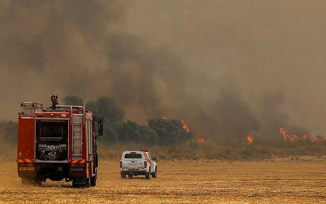 Des pompiers tentent d'éteindre un incendie de broussailles près de Moshav Aderet, le 17 juillet 2019. (Noam Revkin Fenton/Flash90)