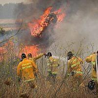 Des pompiers tentent d'éteindre un incendie de broussailles près du Moshav Aderet, le 17 juillet 2019. (Noam Revkin Fenton/Flash90)