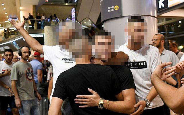 Les adolescents israéliens blanchis d'une accusation de viol en réunion retrouvent les membres de leur famille à l'aéroport Ben-Gurion, le 28 juillet 2019 (Crédit : Flash90)