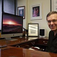 Le Professeur Avi Loeb dans son bureau à Harvard. Son fond d'écran contient une photo de Proxima Centauri, l'étoile la plus proche de notre Soleil. (Rich Tenorio/Times of Israel)