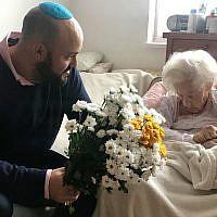 Krystyna Danko reçoit des fleurs de Jonny Daniels dans son appartement de Varsovie, en Pologne, pour son 102ème anniversaire, le 9 juillet 2019 (Crédit : From the Depths via JTA)