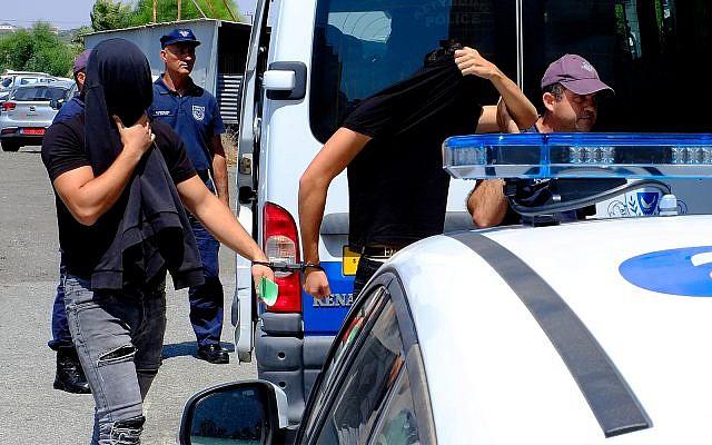 Deux des douze Israéliens soupçonnés de viol couvrent leurs visages à leur arrivée au tribunal de Famagusta, dans la ville de  Paralamni, à Chypre, le 18 juillet 2019 (Crédit :  AP Photo/Petros Karadjias)
