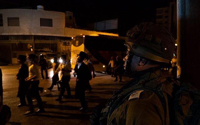 Des soldats israéliens sécurisent des pèlerins juifs au Tombeau de Joseph, près de Naplouse, en Cisjordanie, le 29 juillet 2019. (Armée israélienne)