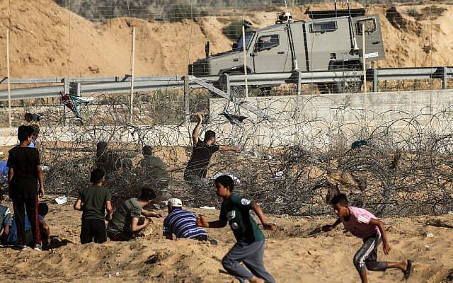 Un manifestant palestinien lance des pierres sur un véhicule de l'armée israélienne lors d'affrontements entre des manifestants palestiniens et des forces israéliennes à travers la barrière de fil barbelé au cours d'une manifestation à la frontière à proximité de Rafah dans le sud de la bande de Gaza, le 19 juillet 2019.   (SAID KHATIB / AFP)