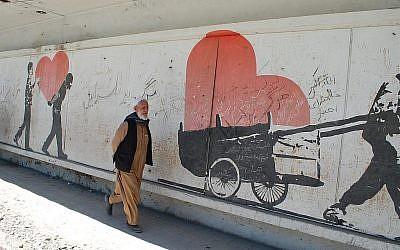 """Un homme afghan à Kaboul passe devant une peinture murale sur le site d'une attentat à la bombe, où l'on peut lire des slogans gribouillés de """"mort à Israël"""".(Ezzatullah Mehrdad/ Times of Israël)"""