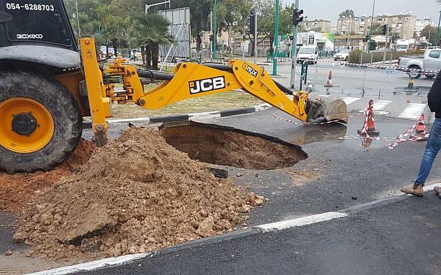 L'image d'un trou géant dans une route, le 14 janvier 2019, après la pluie. (Municipalité de Kiryat Yam)
