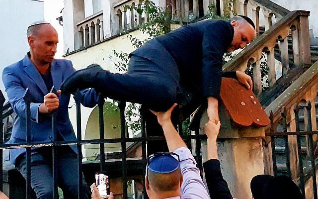 Le grand rabbin polonais Michael Schudrich grimpe sur la clôture d'une synagogue barricadée (Crédit : Shimon Briman/JTA)