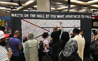 """Des participants à la Palestine Expo 2017 à Lodnres écrivent sur un mur pour dénoncer """"l'apartheid"""" israélien. Crédit : capture écran/YouTube)"""