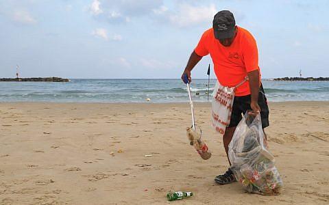 Un employé de la mairie de Tel Aviv ramasse les plastiques et autres déchets laissés sur les plages de la ville côtière israélienne, le 21 juin 2019.(Crédit : JACK GUEZ / AFP)