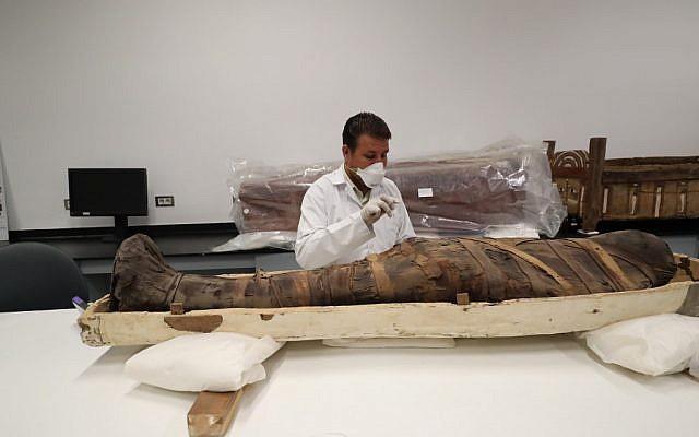 Un archéologue égyptien vérifie une momie durant un travail de restauration sur le sarcophage de Toutankhamon, au musée egyptie, le 4 août 2019. (Crédit : Khaled DESOUKI / AFP)