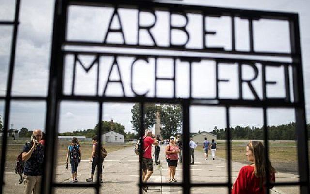 """Des visiteurs devant une grille de fer portant la phrase allemande """"Arbeit Macht Frei"""" («Le travail vous rend libre») dans l'ancien camp de concentration de Sachsenhausen, dans l'est de l'Allemagne, le 7 août 2019. (Crédit : Odd ANDERSEN / AFP)"""