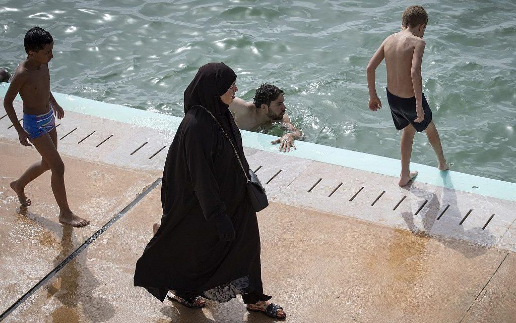 Une Marociane voile passe devant un homme à la nouvelle piscine publique de Rabat, le 7 août 2019. (Crédit ! FADEL SENNA / AFP)
