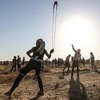 Un manifestant palestinien utilise une fronde pour jeter des pierres durant un affrontement au bord de la frontière avec Israël à l'est de la bande de Gaza, le 16 août 2019 (Crédit : MAHMUD HAMS / AFP)