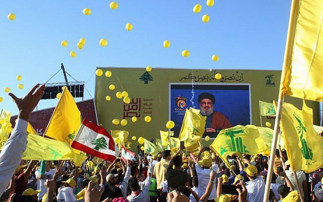 Les partisans du groupe terroriste du Hezbollah agitent le drapeau du groupe lors de la commémoration du 13e anniversaire de la fin de la guerre de 2006 avec Israël dans la ville de Bint Jbeil dans le sud du Liban, le 16 août 2019. (Crédit : Mahmoud ZAYYAT / AFP)