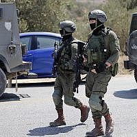 Des soldats israéliens sur le site de l'explosion d'une bombe, près de l'implantation de Dolev, en Cisjordanie, qui a tué une adolescente et blessé deux autres, le 23 août 2019 (Crédit : Ahmad GHARABLI / AFP)