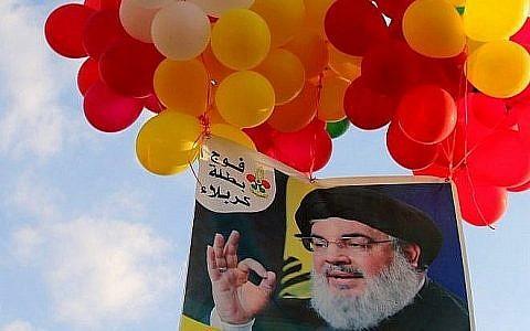 Une photographie du leader du mouvement libanais chiite du Hezbollah attachée à des ballons pendant un rassemblement du groupe terroriste dans la ville d'Al-Ain, dans la vallée du Bekaa, au Liban, le 25 août 2019 (Crédit : AFP)