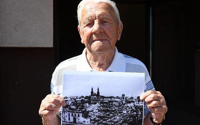 Tadeusz Sierandt, un témoin du bombardement de Wielun tient une photographie de la ville détruite le 20 août 2019. (Crédit : Janek SKARZYNSKI / AFP)