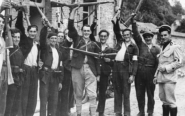 Des combattants de la Résistance française locale agitent leurs fusils en saluant les troupes britanniques dans le village de Quillebeuf, en France, en août 1944. (Photo AP)