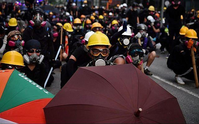 Des manifestants équipés de parapluies et de masque de protection face à la police anti-émeutes dans le quartier de Kowloon Bay à Hong Kong, le 24 août 2019. (Crédit : Lillian Suwanrumpha/AFP/Getty Images/via JTA)