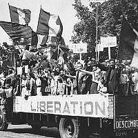 """Un camion chargé de Parisiens qui brandissent des drapeaux français et américains et de panneaux """"Vive De Gaulle"""" dans un paris en liesse, après sa libération,le 28 août 1944. (Crédit : AP Archives)"""