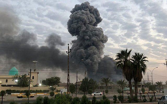De la fumée s'élève après une explosion sur une base militaire au sud-ouest de Bagdad, en Irak, le 12 août 2019. (Crédit : AP Photo/Loay Hameed)