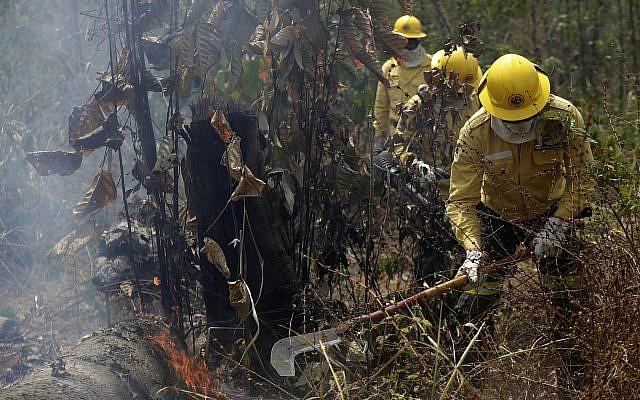 Des pompiers dans la région de Vila Nova Samuel dans la partie brésilienne de l'Amazon, le 25 août 2019. (Crédit : AP Photo/Eraldo Peres)
