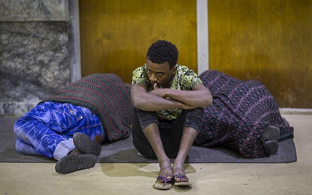 L'éthiopian Zeynu Abebe, 19 ans, est assis entre deux autres migrants à l'aéroport d'Adis Abeba, après avoir été expulsé d'Arabie saoudite, le 22 décember 2017. (Crédit : AP Photo/Mulugeta Ayene)
