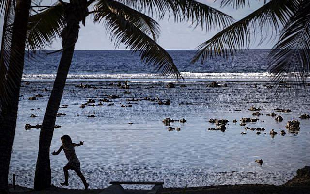 Un enfant joue sur un plage de Nauru, dans les îles du Pacifique, le 3 septembre 2018; (Crédit : Jason Oxenham/Pool Photo via AP)