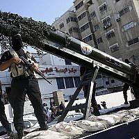 Les membres palestiniens des Brigades  Al-Quds, aile militaire du Jihad islamique palestinien, défilent avec une réplique de roquette sur un camion durant une parade, le 4 octobre 2018 (Crédit :  AP Photo/Adel Hana)