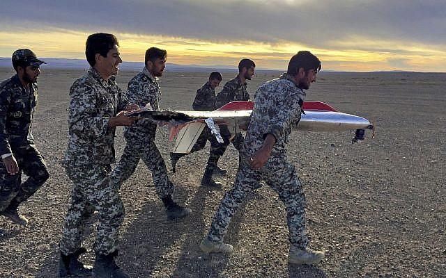 Sur cette photo fournie par l'armée iranienne, des soldats transportent les débris d'un drone durant des exercices à Semnan, en Iran (Crédit : Armée iranienne via AP)