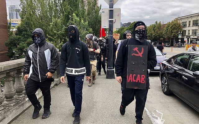 Des contre-manifestants anti-fascistes traversent le pont Burnside à la recherche du groupe d'extrême droite Proud Boys, à Portland, le 17 août 2019. (Crédit : AP Photo/Gillian Flaccus)