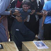 Un Afghan pleur devant les cercueils des victimes d'attentats dans une salle de mariage, à Kaboul, le 18 août 2019. (Crédit : AP/Rafiq Maqbool)