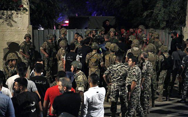 Les forces de sécurité libanaises près du site du crash d'un drone israélien présumé dans un bastion du Hezbollah libanais, dans la banlieue sud de Beyrouth au Liban, le 25 août 2019. (Crédit : AP/Bilal Hussein)