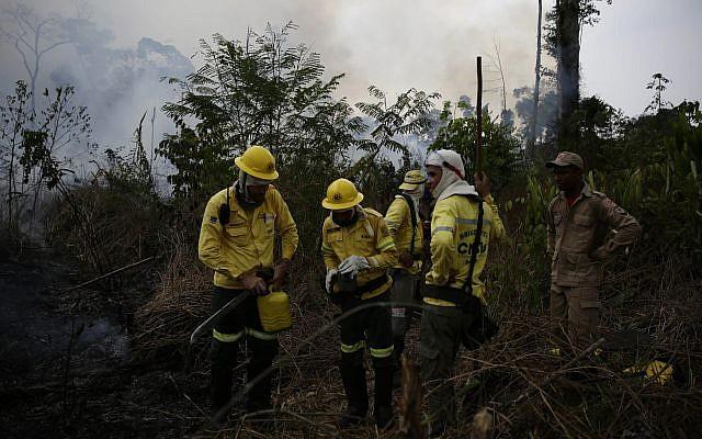 Des pompiers luttent contre les flammes en Amazonie, dans la ville de Port Velho, au Brésil, le 26 août 2019. (Crédit : /Eraldo Peres)