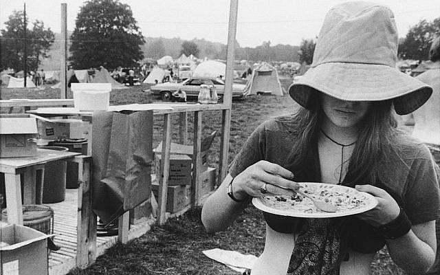 Une jeune femme se sert une ration gratuite dans le camp du festival de musique de Woodstock de Bethel, à New York, le 15 août 1969 (Crédit : AP Photo)