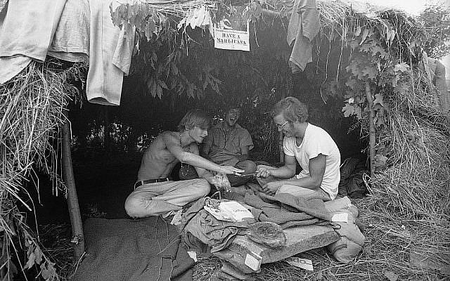 Des fans de musique sous une hutte en herbe au festival d'art et de musique de Woodstock, le 17 août 1969 (Crédit : AP Photo)