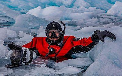 Le photographe Amos Nachoum dans la glace. (Crédit : Keding Zuh)